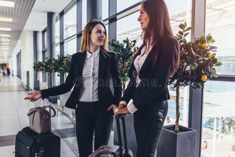 Två gladlynta kvinnliga vänner som väntar på ett plant anseende i flygplatskorridor med tungt bagage nära portarna arkivbild
