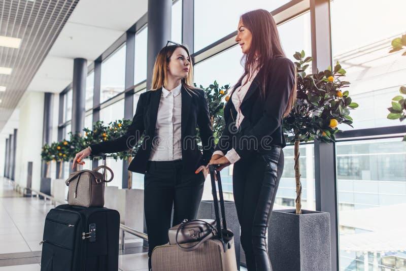 Två gladlynta kvinnliga vänner som väntar på ett plant anseende i flygplatskorridor med tungt bagage nära portarna royaltyfri bild