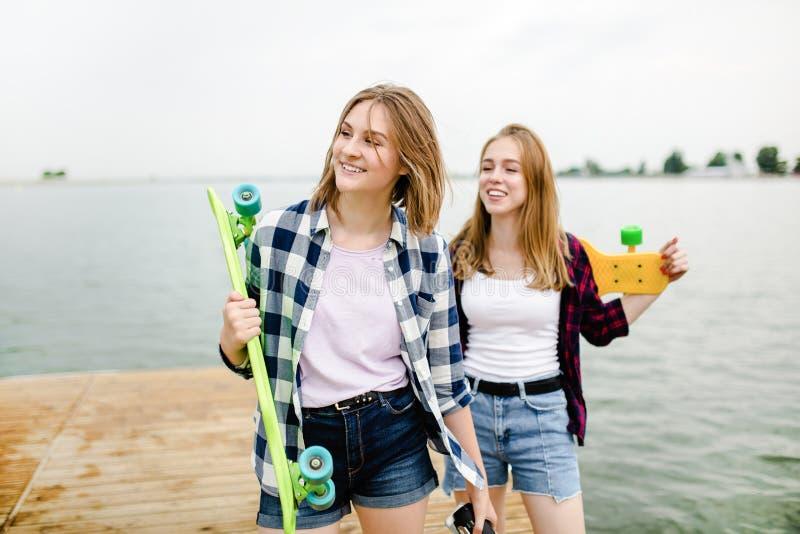 Två gladlynta lyckliga skateboradåkareflickor i hipsterdräkten som har gyckel på en träpir under sommarsemester royaltyfri bild