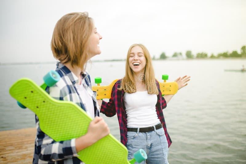 Två gladlynta lyckliga skateboradåkareflickor i hipsterdräkten som har gyckel på en träpir under sommarsemester royaltyfri foto