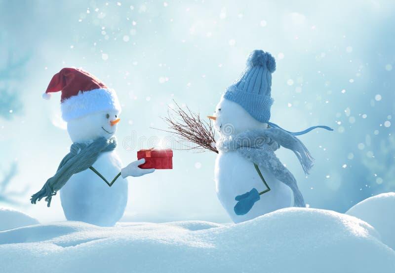 Två gladlynta snögubbear som står i vinterjullandskap arkivfoton