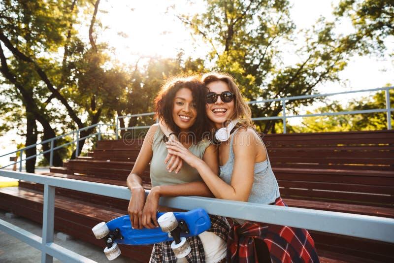 Två gladlynta unga flickor med skateboarden royaltyfri foto