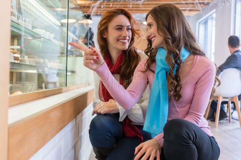Två gladlynta unga kvinnor framme av ställa ut av ett modernt kafé arkivfoto