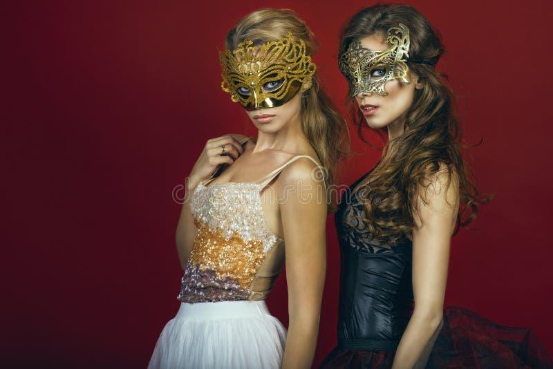 Två glam ursnygga kvinnor, blondin och brunett, i guld- och brons maskerar bärande aftonkappor fotografering för bildbyråer