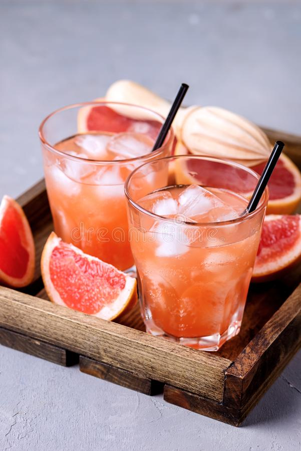 Två glasögon av Tasty Grapefruit Cold Drink eller Cocktail på träfat på träfat Refreshment Beverage Gray Background Cold Grapefru royaltyfri foto