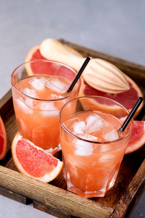 Två glasögon av Tasty Grapefruit Cold Drink eller Cocktail på träfat på träfat Refreshment Beverage Gray Background Cold Grapefru royaltyfria bilder