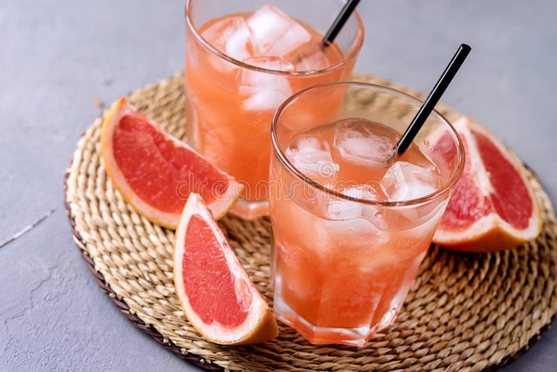 Två glas av Tasty Grapefruit Cold Drink eller Cocktail Refreshment Beverage Gray Background Cold Grapefruit Juice ovanför horison arkivbilder