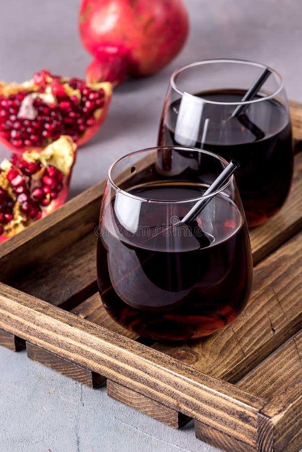 Två glas färsk tasty pomergranatjuice på grå bakgrund Diet Hälsosam dryck Detox Ripe Pomegranate Trä Track Vertical royaltyfri fotografi