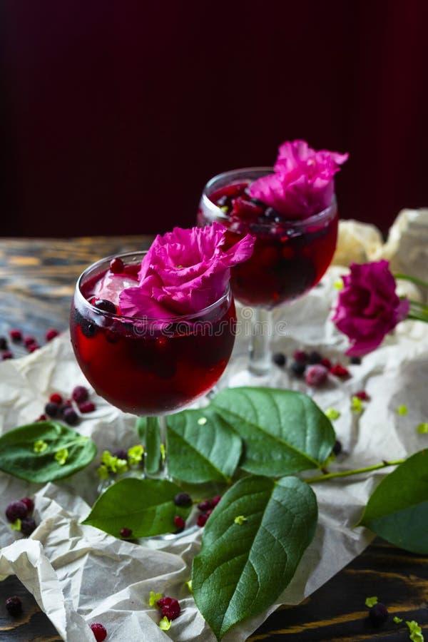 Två glases mycket av den röda drinken med bär, is och en rosa blomma royaltyfri fotografi