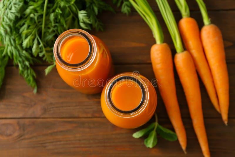 Två glasflaskor av ny fruktsaft med morötter fotografering för bildbyråer