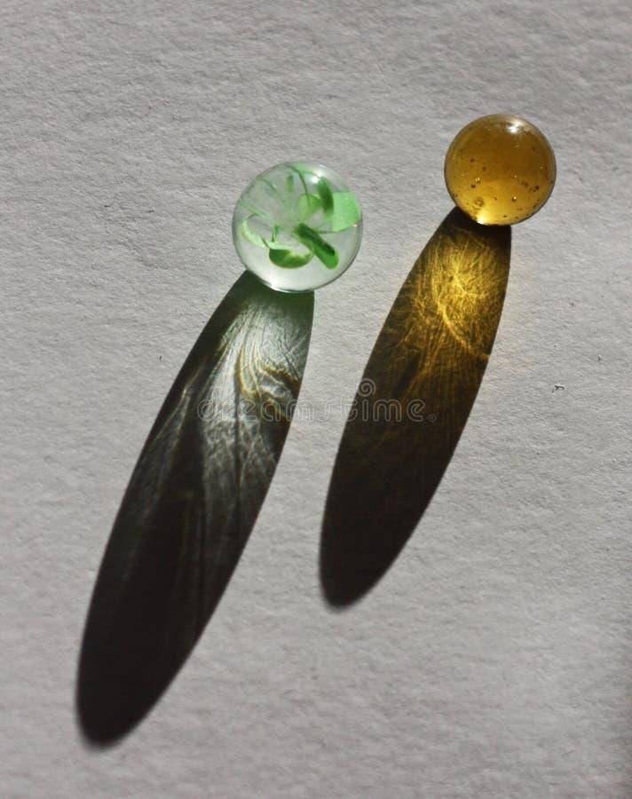 Två glass pärlor på papper med panelljuset och skuggor royaltyfri fotografi