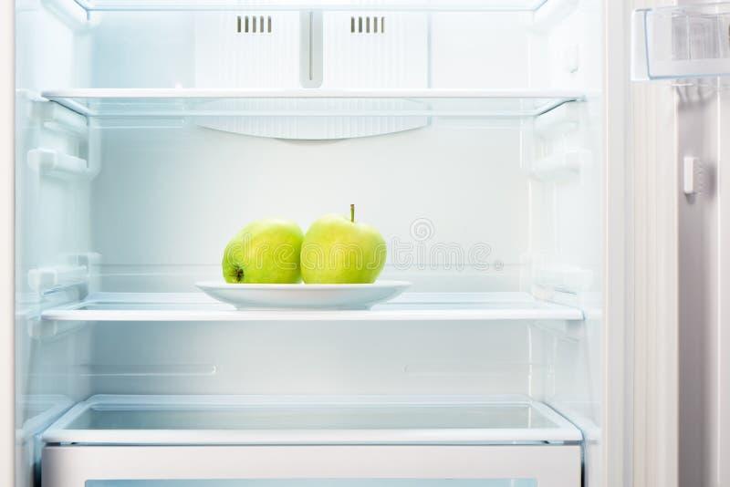Två gröna äpplen på den vita plattan i öppet tomt kylskåp fotografering för bildbyråer