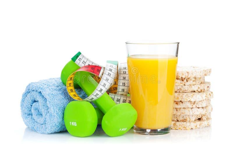 Två gröna dumbells, måttband och sund mat Kondition och H royaltyfria foton