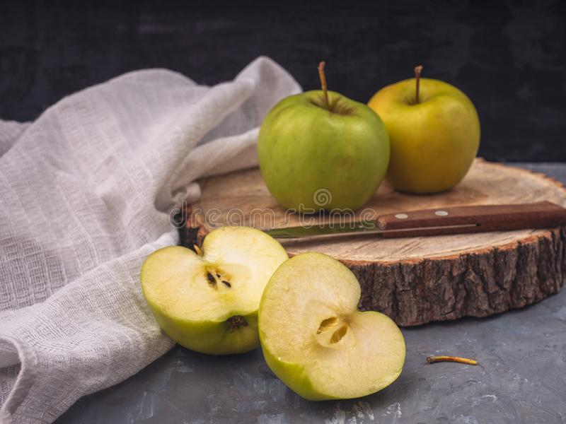 Två gröna guld- äpplen och två halvor på ett träuppläggningsfat och en grå bakgrund, vit servett för bomull, kökkniv royaltyfri fotografi