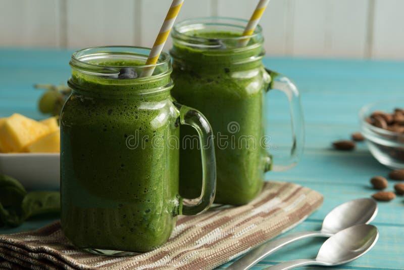 Två gröna smoothies av grönkål och spenat i murarekrus rånar på en t royaltyfria foton