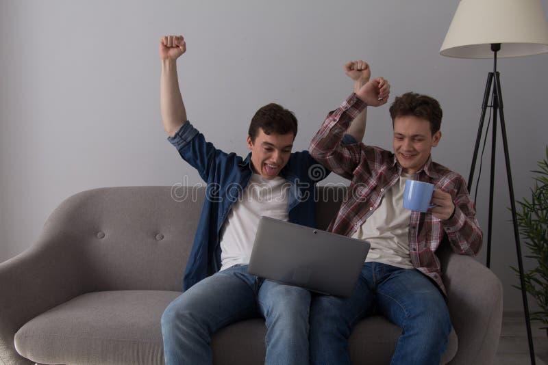 Två grabbar med bärbara datorn på soffan royaltyfri bild
