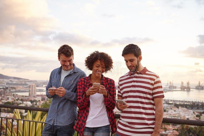 Två grabbar och en flicka som ser mobiltelefoner arkivfoton
