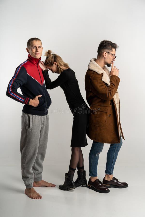 Två grabbar och flicka i stilfull tillfällig ljus och mörk färgrik kläder fotografering för bildbyråer