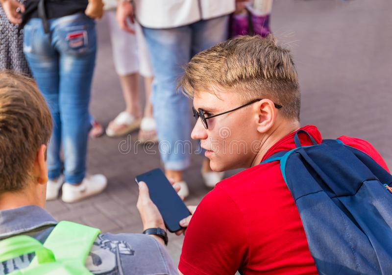 Två grabbar sitter på på en bänk och håller ögonen på något i smartphonen royaltyfri fotografi
