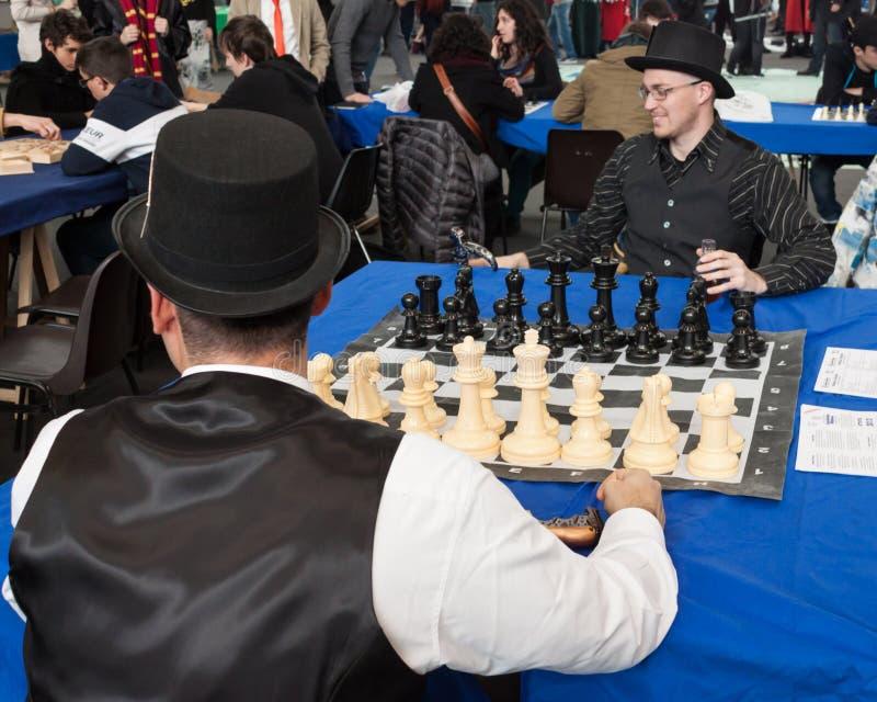 Två grabbar spelar schack på den Festival del Fumetto regeln i Milan, Italien arkivbilder