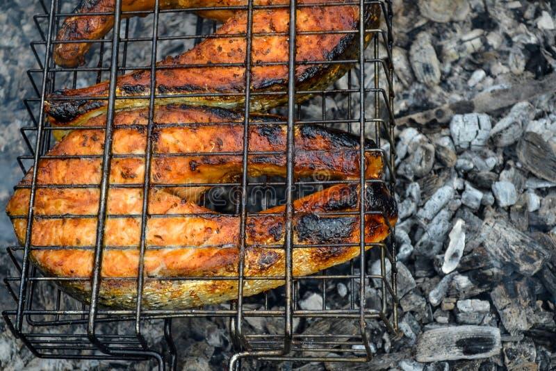 Två grillade laxbiffar Bränner till kol ett stycke av aptitretande fiskbiff som bakas i kol arkivfoto