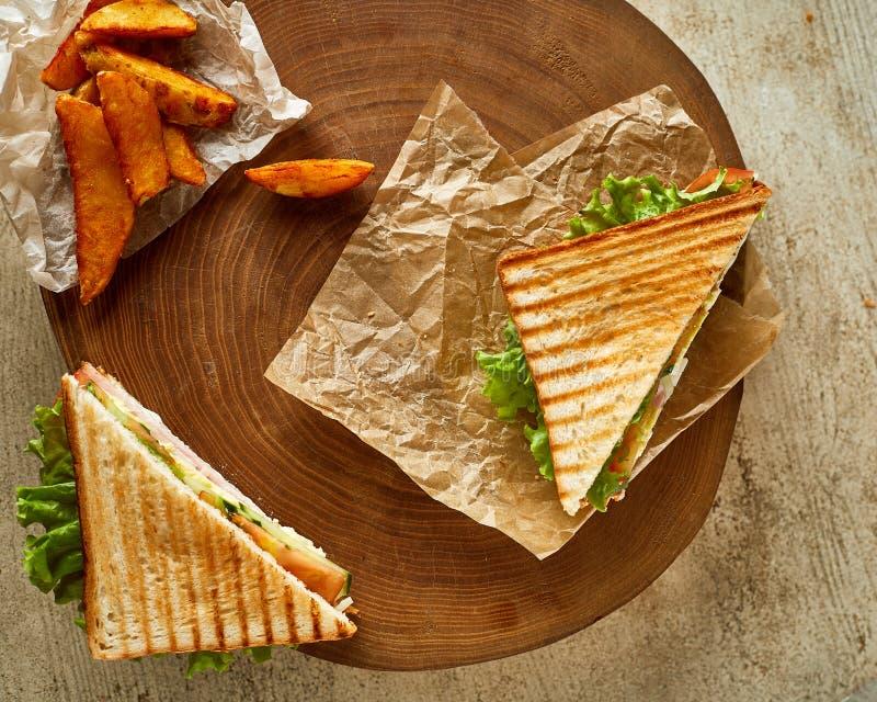 Två grillade smörgåsar som tjänas som på trä med den stekte frasiga potatisen royaltyfri fotografi