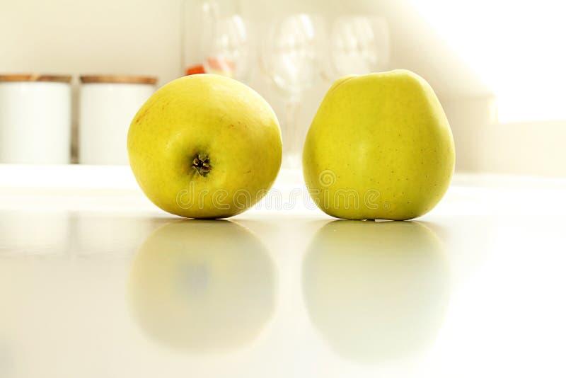 Två gula äpplen i kök arkivfoto