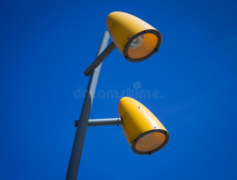 Två gula gatalampor med blå himmel royaltyfria bilder