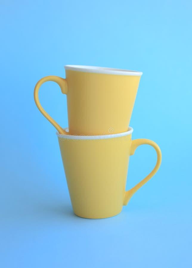 Två gula koppar på blått royaltyfria bilder
