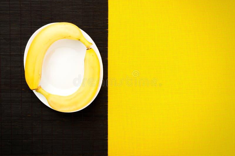 Två gula mogna bananer från vändkretsarna på en napki för svart bambu arkivfoto