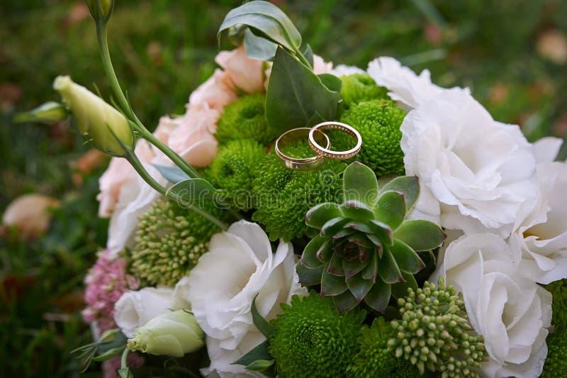 Två guld- cirklar på en bride& x27; s-bröllopbukett arkivfoto