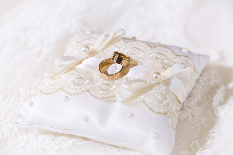 Två guld- skinande vigselringar på satäng snör åt tillsammans kudden royaltyfri bild