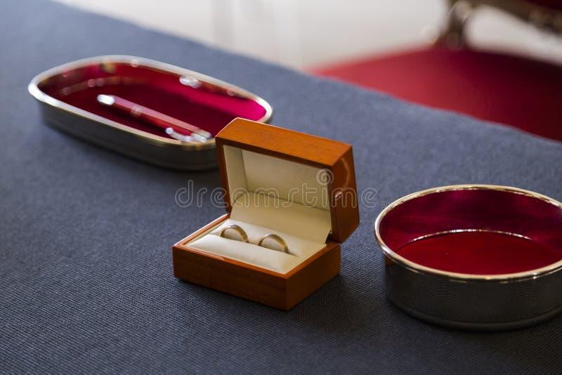 Två guld- skinande vigselringar tillsammans i träcasket arkivbild
