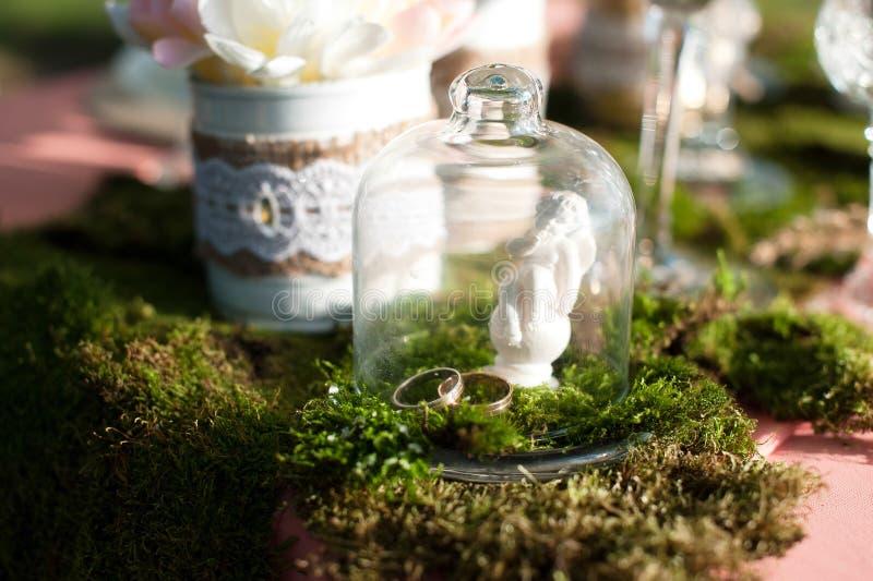 Två guld- vigselringar på en tabell under ett exponeringsglas av exponeringsglas N?rbild royaltyfria bilder