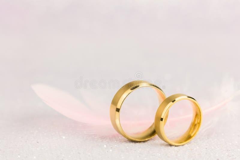 Två guldbröllopcirklar och ljusa Angel Feather arkivbilder