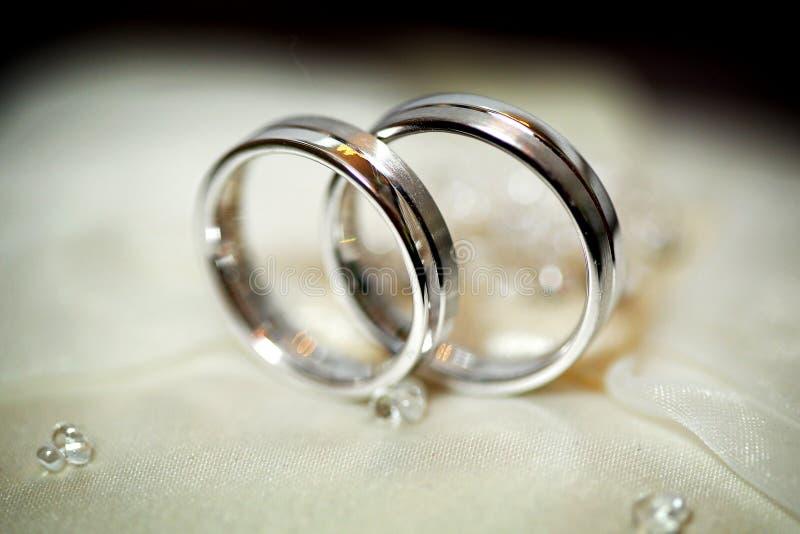 Två guldbröllopcirklar på en beige satäng gifta sig för trappa för stående för brudbegreppsklänning royaltyfri bild