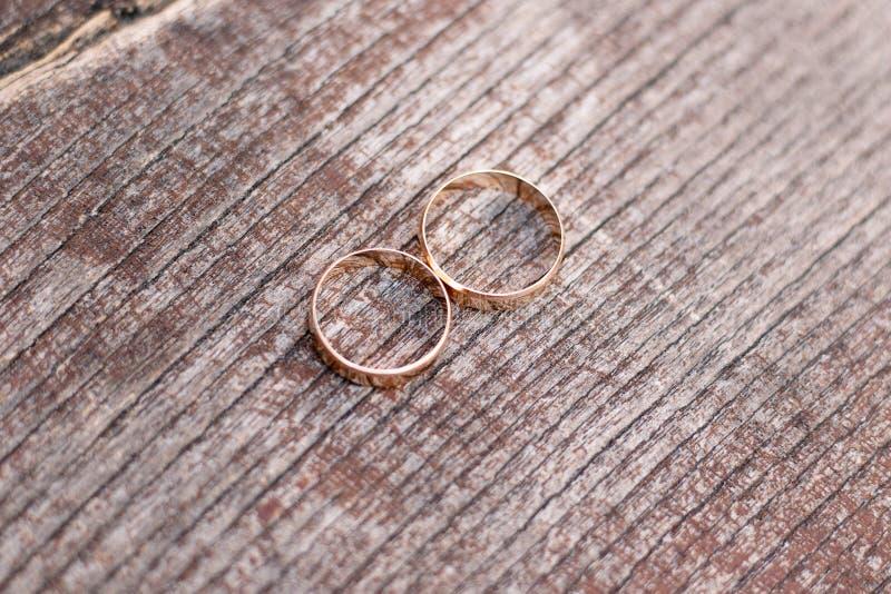 Två guldbröllopcirklar på träbakgrund royaltyfria bilder