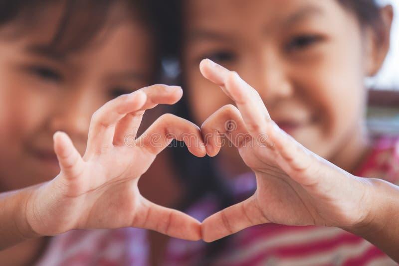 Två gulliga asiatiska barnflickor som tillsammans gör hjärtaform med händer royaltyfria foton