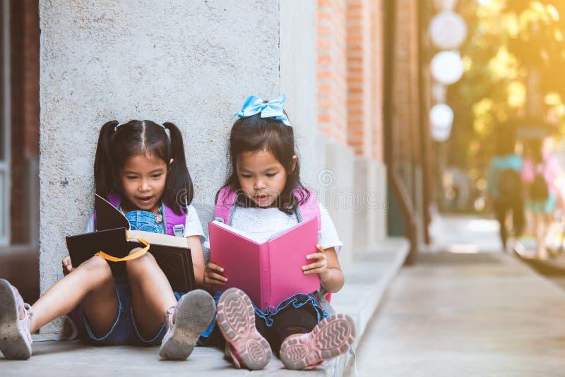 Två gulliga asiatiska elevflickor som tillsammans läser en bok i skolan med gyckel och lycka royaltyfri bild