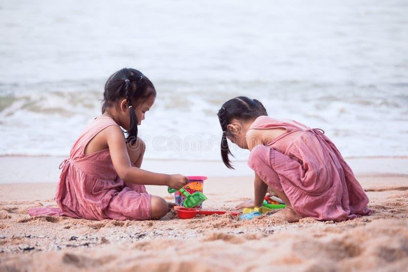 Två gulliga asiatiska flickor för litet barn som har gyckel som spelar med sand arkivbilder
