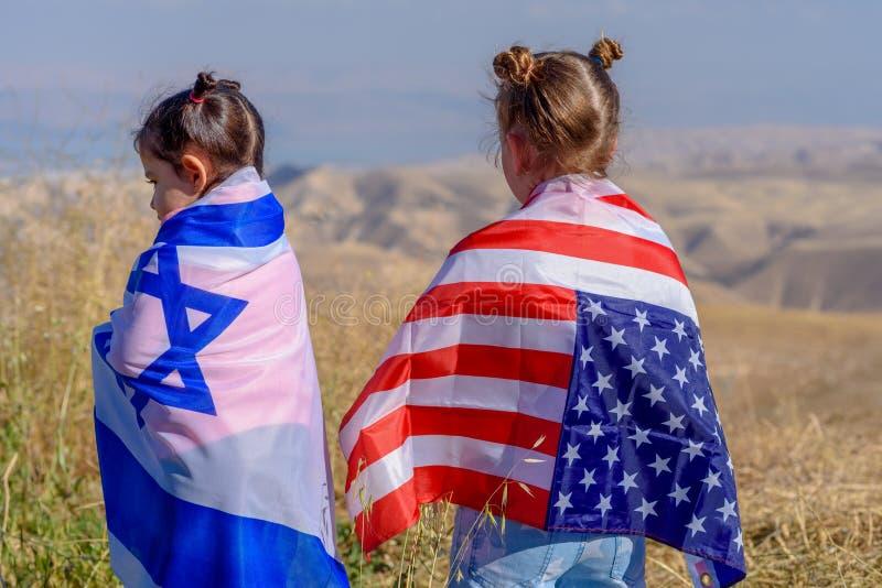 Två gulliga barn med amerikan- och Israel flaggor royaltyfri fotografi