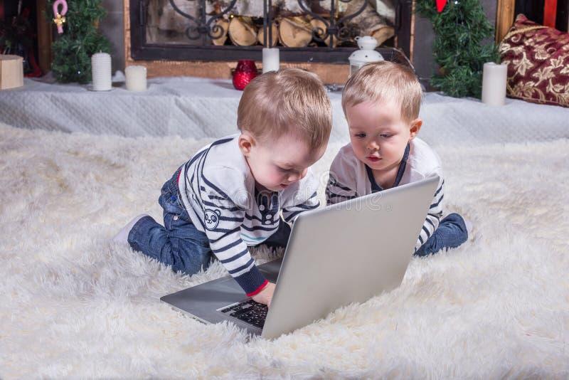 Två gulliga barn som använder bärbara datorn royaltyfri foto