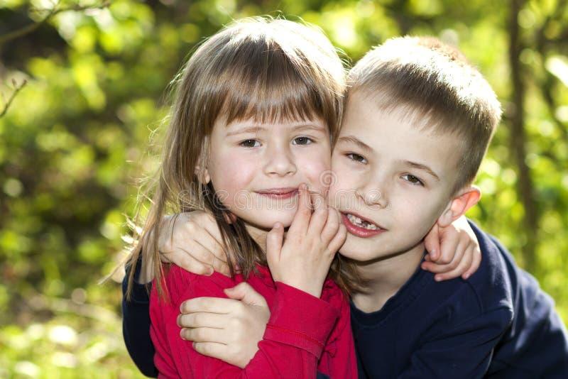 Två gulliga blonda roliga lyckliga le barnsyskon, ung pojkebroder som omfamnar systerflickadet fria på ljus solig grön bokeh arkivbilder