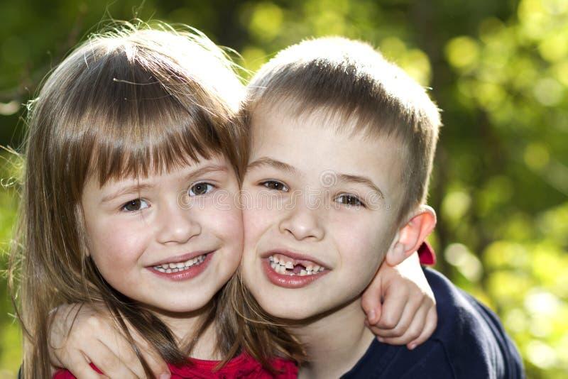 Två gulliga blonda roliga lyckliga le barnsyskon, ung pojkebroder som omfamnar systerflickadet fria på ljus solig grön bokeh royaltyfri bild