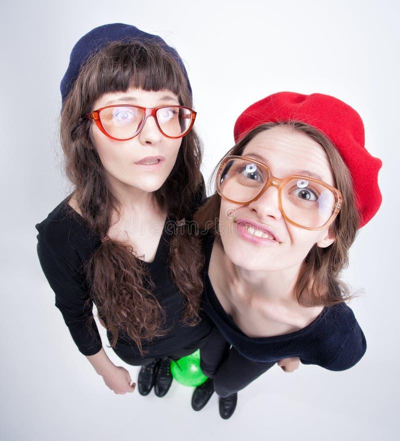 Två gulliga flickor som bär farmors exponeringsglas som gör roliga framsidor fotografering för bildbyråer