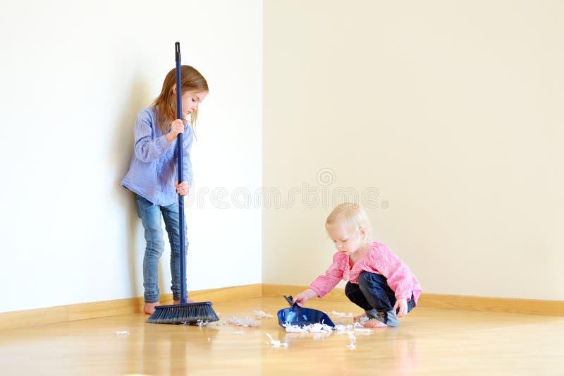 Två gulliga flickor som hjälper hennes mamma att göra upp ren royaltyfria foton
