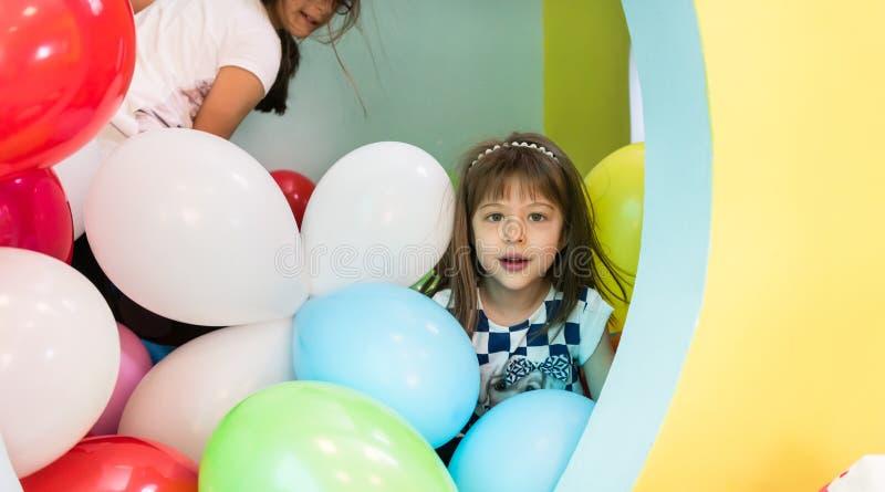 Två gulliga flickor som talar, medan spela med mångfärgade ballonger royaltyfria foton