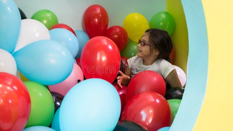 Två gulliga flickor som talar, medan spela med mångfärgade ballonger royaltyfri fotografi