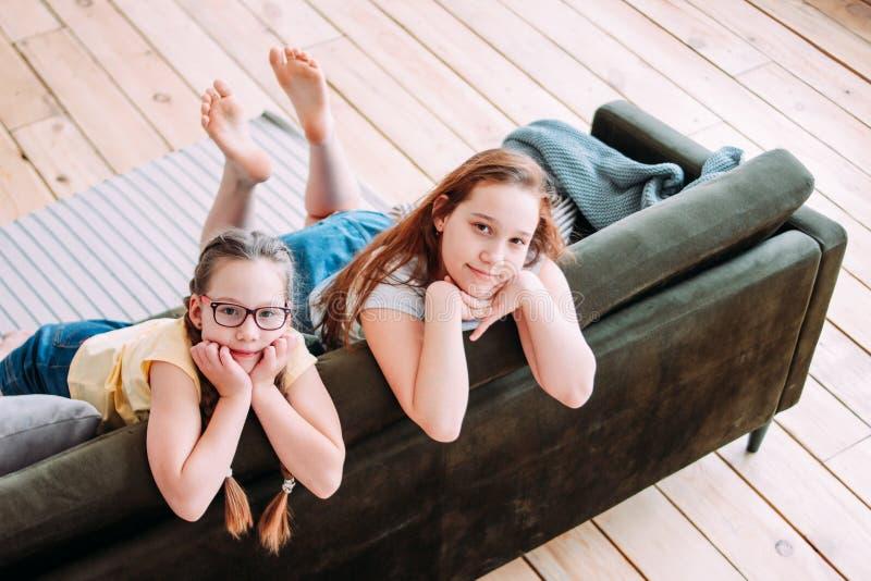 Två gulliga le tweens för flickabarnvänner som hemma sitter på soffan arkivfoto