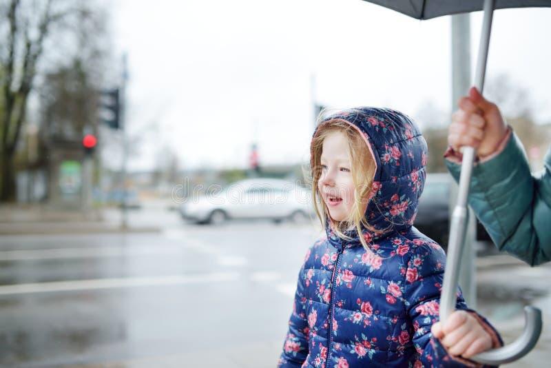 Två gulliga lilla systrar som går under paraplyet arkivbild